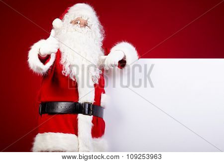 Santa Claus pointing in white blank sign with smile,christmas  red background
