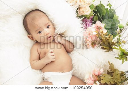 Cute Baby Girl Lying On Fur Blanket With Flowers Around
