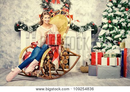 Charming young woman celebrating Christmas at home by the fireplace and a tree, beautifully decorated for Christmas.