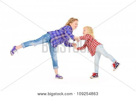 Older and younger sisters playing together and laughing. Happy childhood. Family concept. Isolated over white.