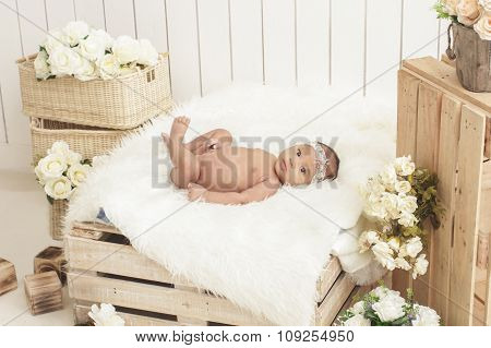 Adorable Baby Girl Lying On Wooden Box With Fur Blanket