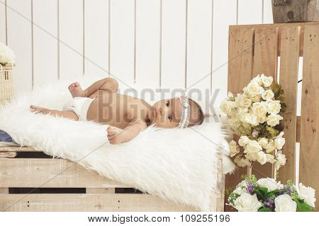 Cute Baby Girl Wearing Headbands Lying On Wooden Box With Fur Blanket