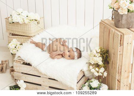 Cute Little Baby Girl Wearing Headbands Lying On Fur Blanket With Flowers Around