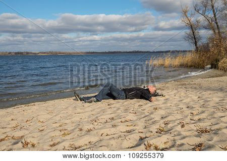 Hiker Man Relaxing On The Beach, Lying On The Sand, Smiling Looking At The Sky And Enjoying Life