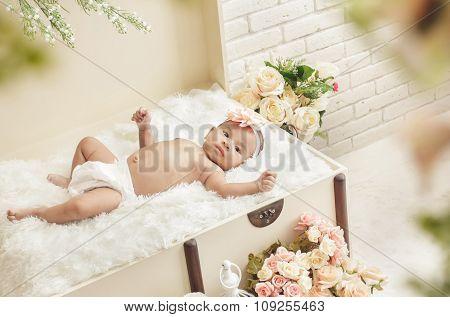 Cheerful Baby Girl Feel Comfortable Lying On Crate With Fur Blanket
