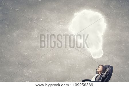 Thoughtful businesswoman in chair and cloud bubble above her head