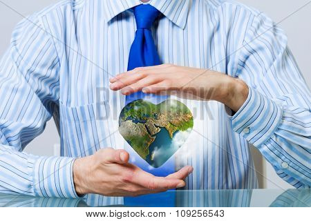 Businessman hands holding heart shaped Earth planet. Elements of this image are furnished by NASA