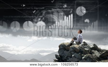Young smiling businessman sitting alone on rock top