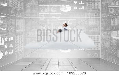 Young businessman sitting on cloud in room and infographs on wall