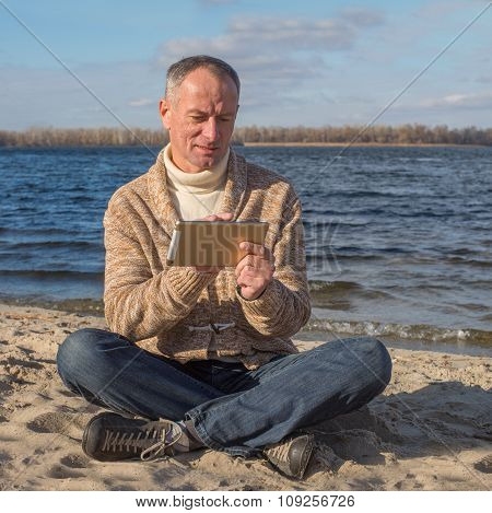 Enthusiastic Man, Wearing Casually, Using His Tablet While Relaxing At The Coast