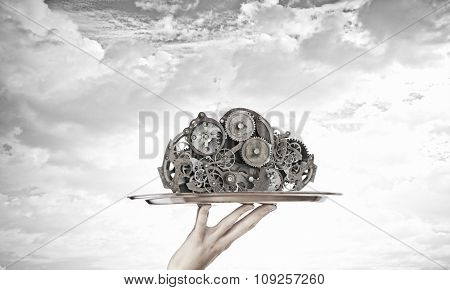 Hand serving metal gears on silver tray