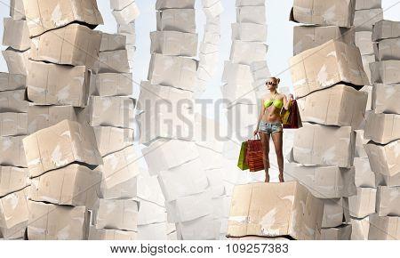 Beautiful young girl in bikini with shopping bags on pile of carton boxes