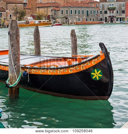 Colorful venetian gondola boat parked in the water, houses and canal view