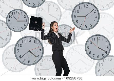 Businesswoman floating among clocks.