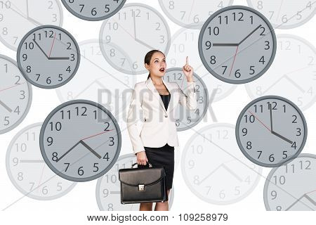 Businesswoman stands among clocks.