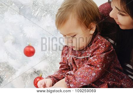 Close Up Portrait Of Little Baby Girl And Her Mother Near Christmas Tree