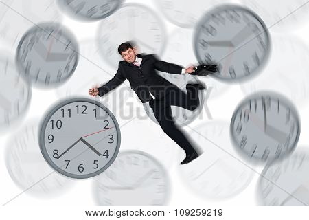 Businessman running late with among big clocks