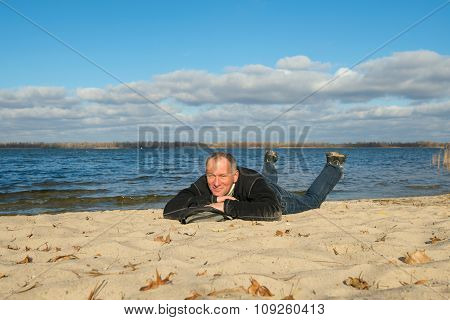 Hiker Man Relaxing On The Coast, Lying On The Sand, Smiling Looking At The Camera And Enjoying Life