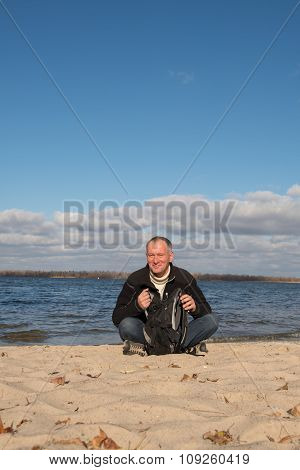 Hiker Man Resting On The Coast, Smiling Looking At The Contents Of His Backpack
