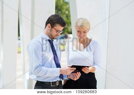 Businesspeople having a meeting outdoors with tablets.