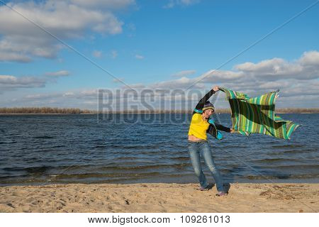 Joyful Expressive Woman Having Fun, Catches The Wind, Playing With Coverlet In The Beach