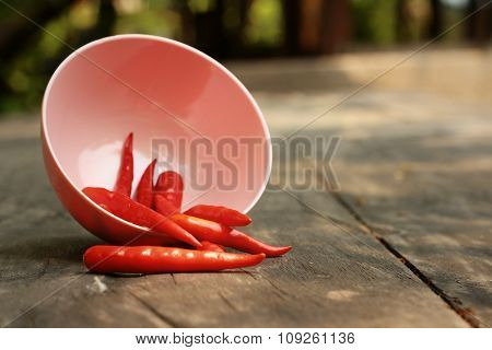 Red Chilies In A Pink Bowl On Wooden Background