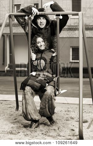 Happy young fashion couple on the swing