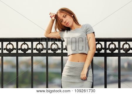Sad young fashion woman at the cast iron fence
