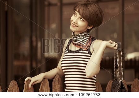 Happy young fashion woman with handbag at the mall window