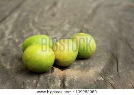 Green Lemons On A Background Of Wood
