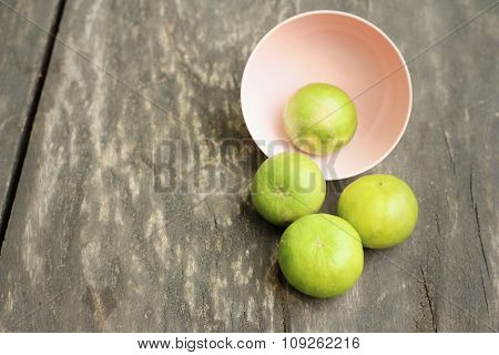 Lemons In A Pink Bowl On A Wood Background