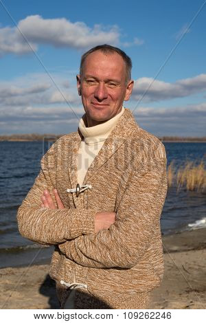 Joyful Expressive Man, Wearing Casually, Standing On The Coast In Magic Autumn Day Posing For Camera