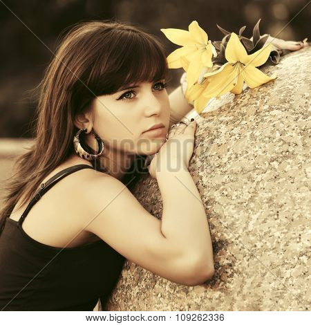 Sad young woman with a flowers daydreaming outdoor
