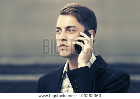 Young fashion business man calling mobile phone on city street