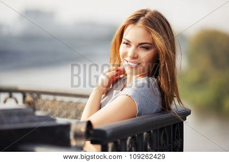 Happy young fashion woman at the cast iron fence