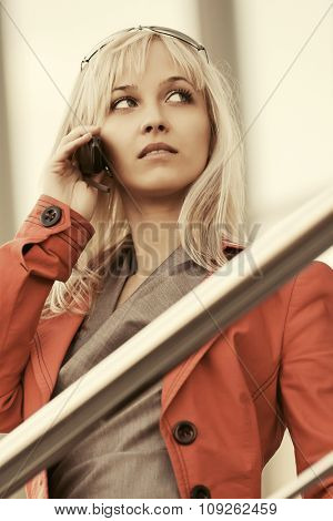 Young blond fashion woman in red jacket calling on cell phone