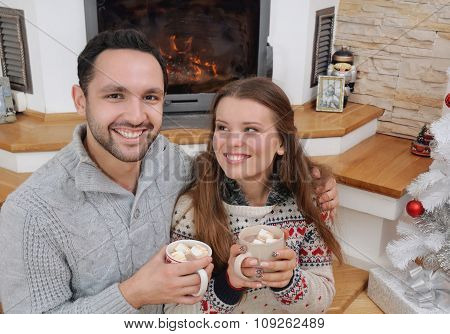 Young Happy Couple With Hot Cocoa Drink In Comfy Sweaters Sitting Near Fireplace
