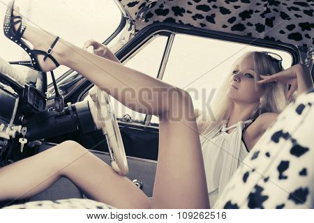 Young fashion blond woman relaxing in retro car
