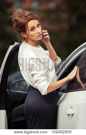 Young fashion business woman calling on mobile phone beside a car