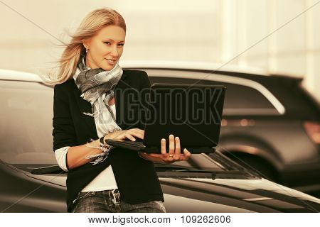 Young fashion blond business woman with laptop next to her car