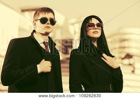 Young fashion business man and woman walking on city street