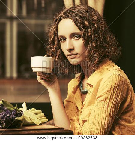 Sad young fashion woman drinking tea at restaurant