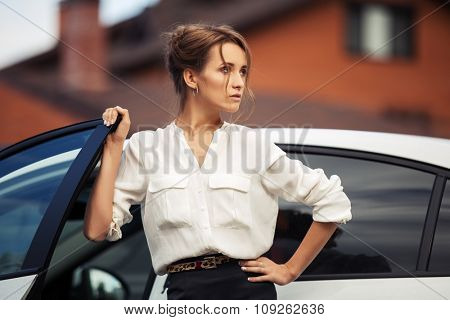 Young fashion business woman standing beside her car