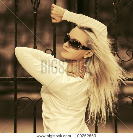 Young fashion blond woman in sunglasses at the cast iron fence