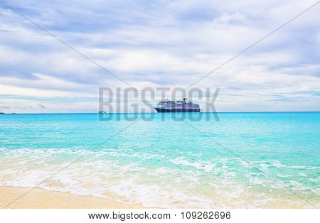 Cruise Ship And Tender On A Light Blue Sea At Half Moon Cay In The Bahamas Under Cloudy Skies