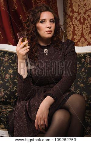 Woman In A Black Dress Sitting In The Dark Room