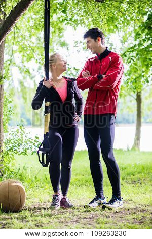 Couple having break from sling training