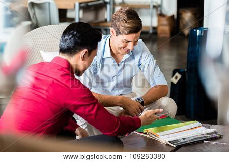 Customer and shop assistant in furniture store planning furnishing of home together