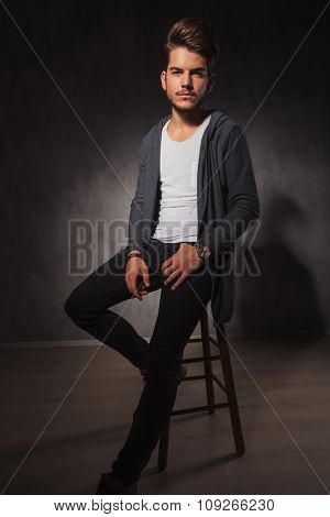 portrait of a skinny guy posing in studio while sitting with hand in pocket