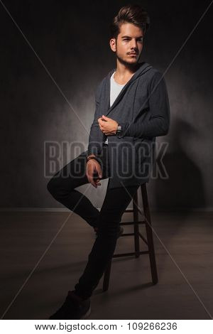 young male model posing in studio while arranging his jacket and looking away